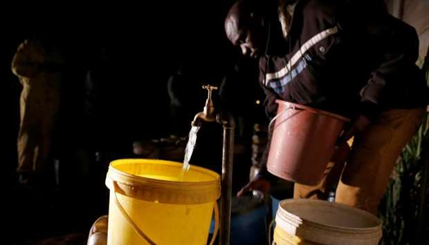 Residents collect water at night from an electric-powered borehole, as the country faces 18-hour dai