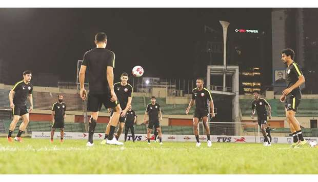 Members of the Qatar team train under the watchful eyes of coach Felix Sanchez (R).