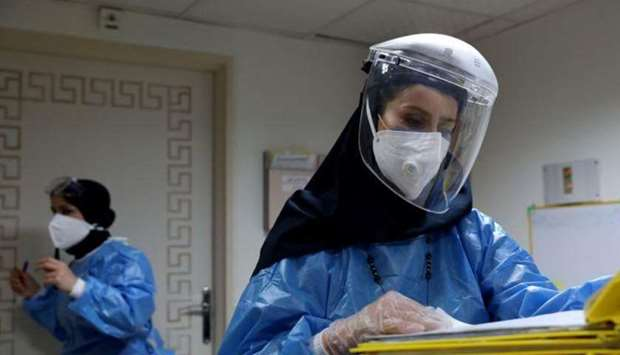A nurse wearing a protective suit and mask checks the files at Hazrate Ali Asghar Hospital.
