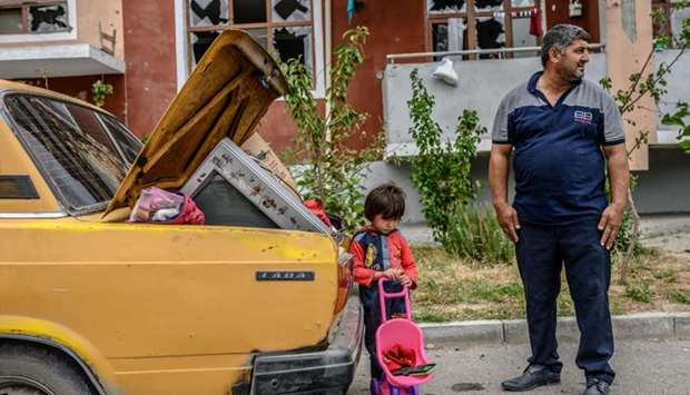 A man stands with his kid by a car outside a damaged apartment building after the family took their