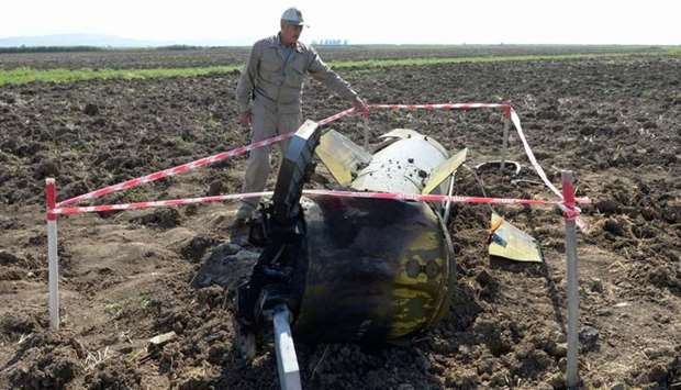 A man stands by what is said is the remains of a Tochka U missile in a field in Fizuli district, Aze