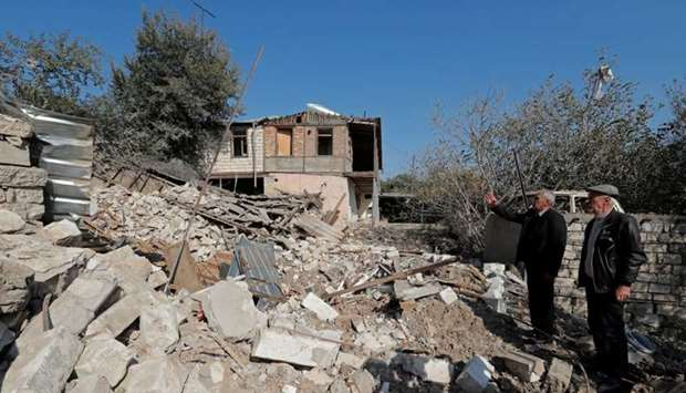 Men stand next to the ruins of a house that was destroyed by recent shelling during the military con