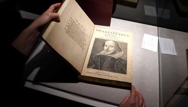 An employee of Christie's auctions holds a 1663 rare first folio of 36 Shakespeare works that was so