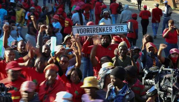 A supporter of Economic Freedom Fighters (EFF) holds a street sign outside the Senekal magistrate's