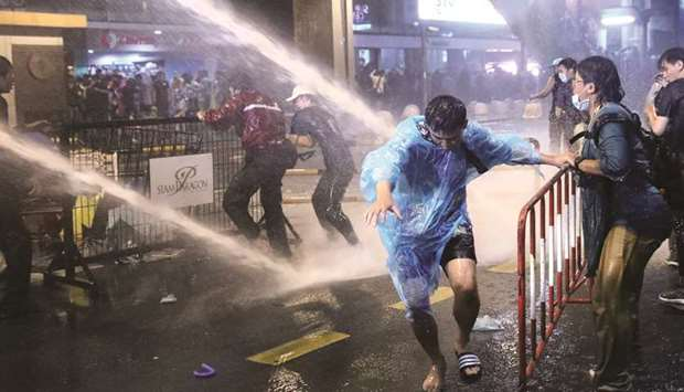 People are hit with water from water cannons during anti-government protests, in Bangkok, yesterday.