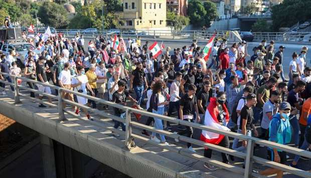 Lebanese demonstrators wave the national flag during a demonstration, marking the first anniversary