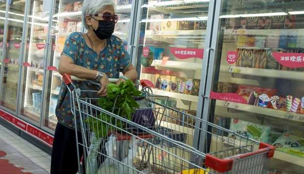 A woman looks at frozen food products in a supermarket in Beijing, China, on August 13, 2020