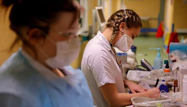 Nurses, wearing a protective mask and a protective suit, work in a Covid-19 medicine unit where pati