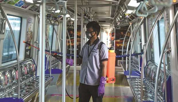 An employee sanitises a coach as the Mumbai Metro network prepares to resume services after more tha
