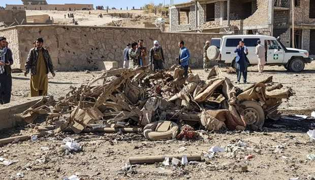 Security personnel and residents gather around the site of a car bomb attack that targeted an Afghan