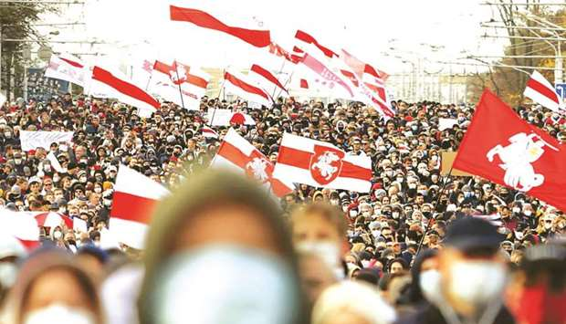 Opposition supporters, carrying former white-red-white flags of Belarus, parade through the streets