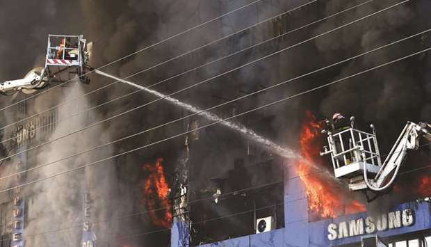 DAMAGE-CONTROL: Firefighters try to extinguish a fire that broke out in a four-storey commercial bui