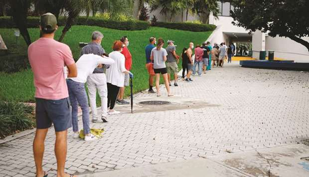 Voters wait in line to cast their early ballots at Miami Beach City Hall in Miami Beach, Florida, ye