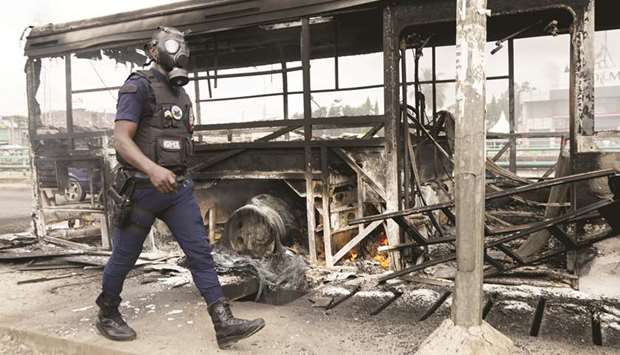 A riot police member walks next to a bus which was burned early in the morning by protesters against