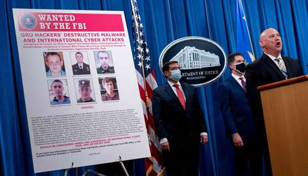 A poster showing six wanted Russian military intelligence officers is displayed as FBI Special Agent