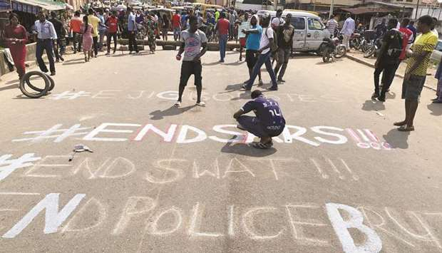A demonstrator paints 'End Sars', referring to the Special Anti-Robbery Squad police unit, on a stre