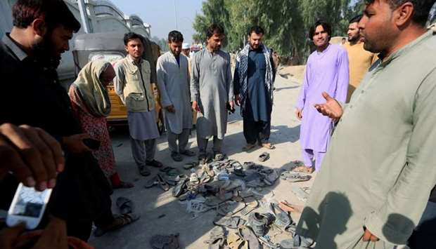 Afghan people stand over abandoned shoes of those who attended collecting tokens needed to apply for