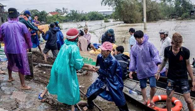 Local residents and volunteers deliver aid packages to residents affected by heavy flood in Quang An