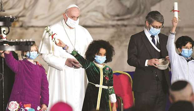 Pope Francis stands as young faithfuls wave during a ceremony for peace with representatives from va