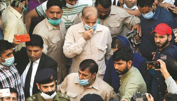 Security officials escort Opposition Leader Shahbaz Sharif (centre) as he leaves the National Accoun