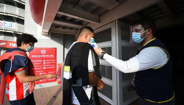 An employee takes the temperature of a soccer fan as he arrives to attend the first Mexican league m