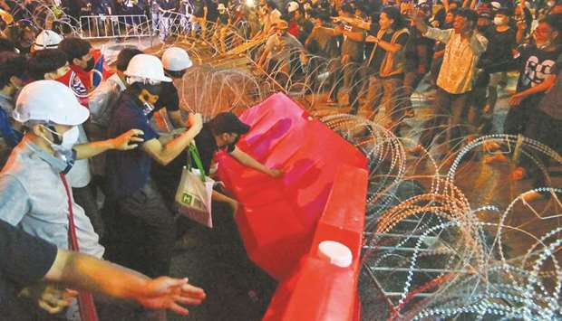 Pro-democracy protesters tear down sections of a barricade during an anti-government rally in Bangko