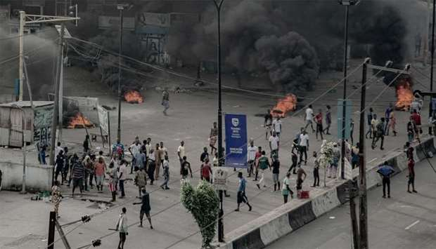 People are seen near burning tires on the street, in Lagos, Nigeria