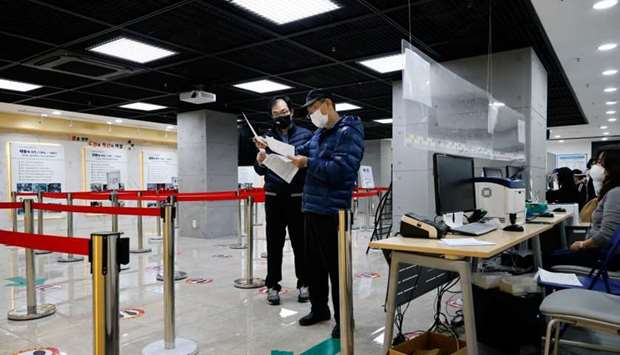 Men check a mandatory document to get an influenza vaccine at a branch of the Korea Association of H