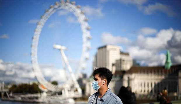 A man wearing a protective face mask walks across Westminster bridge, during the coronavirus disease