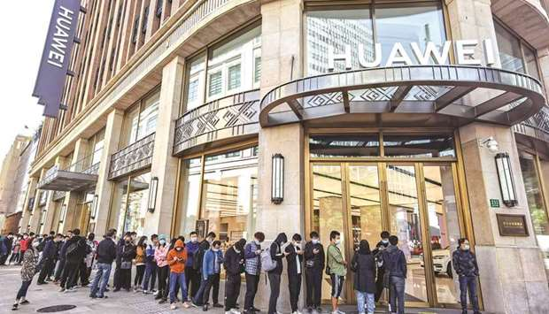 People wearing masks wait in line in front of Huawei's flagship store for pre-sales of the newly lau
