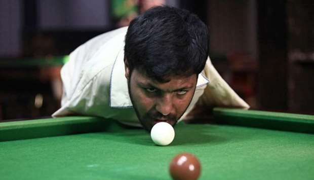 Muhammad Ikram, 32, who was born without arms, plays snooker with his chin at a local club in Samund