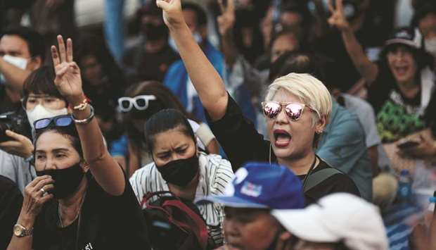 Pro-democracy protesters hold up the three-finger salute outside Bangkok Remand Prison yesterday, as
