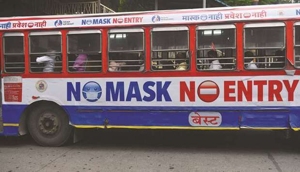 Passengers travel on a bus which has a precautionary message pasted on it against the spread of coro