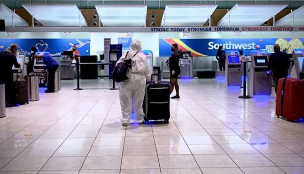 In this file photo taken on October 21, 2020 a woman in a full hazmat suit checks in for her flight