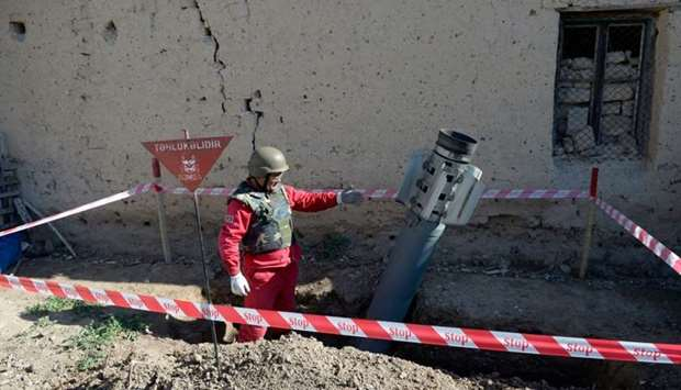 An officer shows a Smerch rocket before demining it in the village of Tap-Qaragoyunlu some 60 km fro