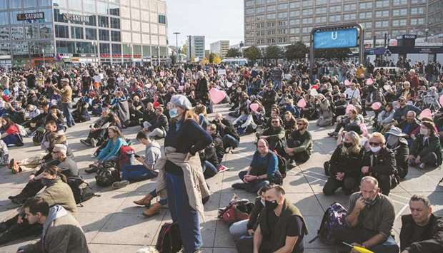 People take part yesterday in a rally against coronavirus restrictions at Berlin's Alexanderplatz.