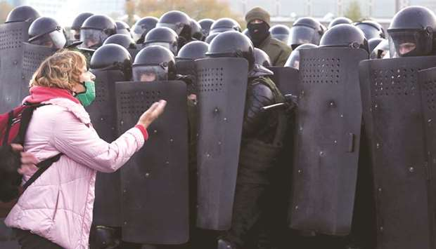 A woman argues with law enforcement officers during an opposition rally in Minsk.