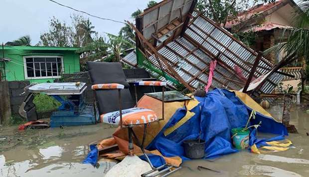 A destroyed house lies on its side after tropical storm Molave hit the town of Pola, Oriental Mindor