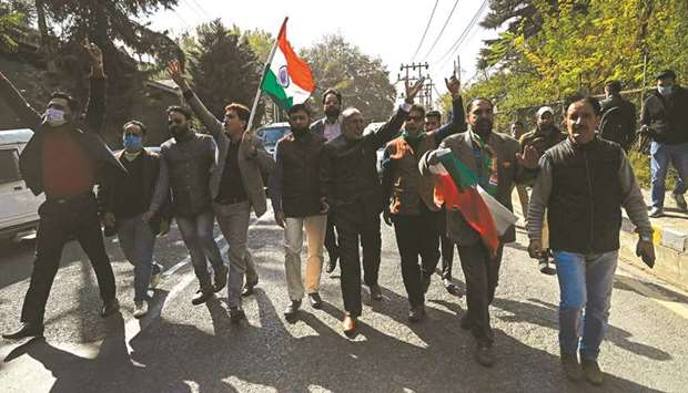 Bharatiya Janata Party (BJP) activists wave a national flag during a demonstration outside the resid