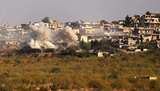 Smoke plumes rise from buildings in the village of Kansafra, in the southern countryside of Syria's