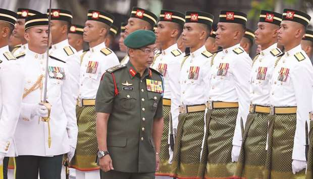Malaysia's King, Al-Sultan Abdullah inspects a guard of honour.