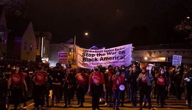 Protesters march through West Philadelphia on October 27, 2020, during a demonstration against the f