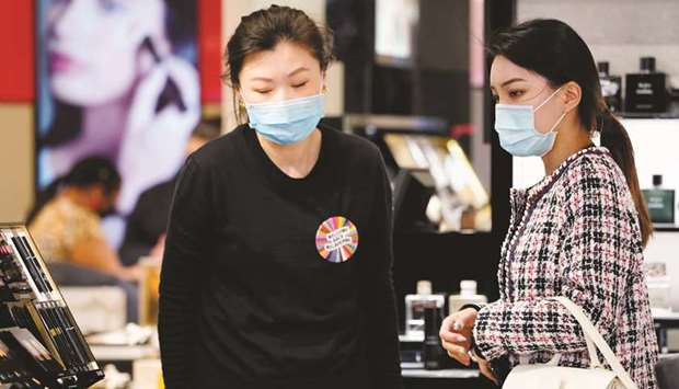 A shopper wearing a face mask is assisted in a retail store after Covid-19 restrictions were eased f