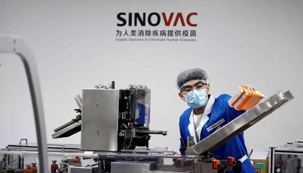 A man works in the packaging facility of Chinese vaccine maker Sinovac Biotech, developing an experi