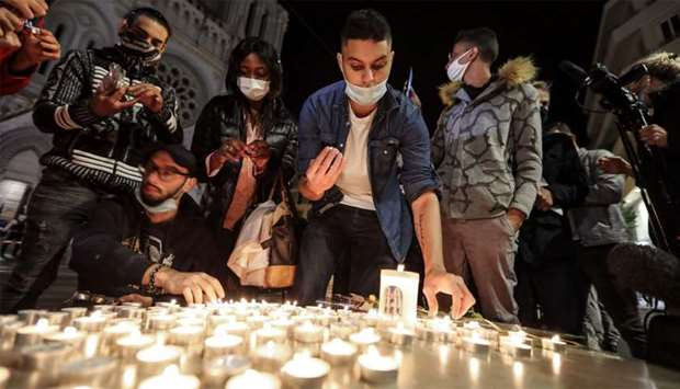 People lights candle outside the Notre-Dame de l'Assomption Basilica in Nice in tribute to the three