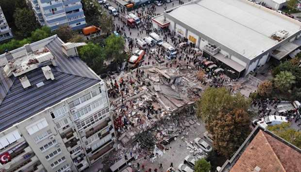 Rescuers search for survivors at a collapsed building after a powerful earthquake struck Turkey's we