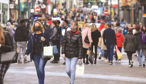 Shoppers walk wearing face masks in the centre of Leeds, West Yorkshire, northern England, yesterday