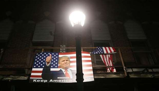 A poster of President Donald Trump is displayed along a street in Winterset, Iowa.