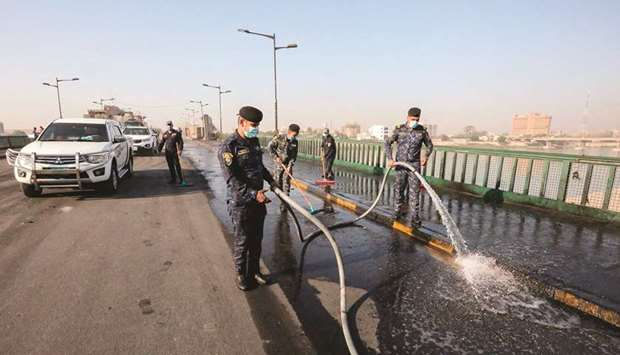 Members of the Iraqi security forces clean with a hose a section of the Jumhuriyah bridge across the