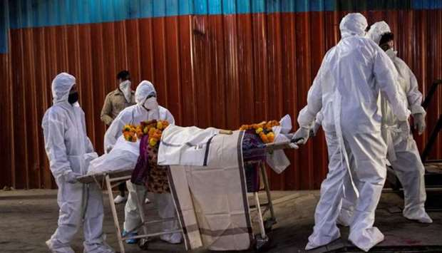 Health workers pull a stretcher with the body of a woman at a crematorium in New Delhi, India.